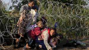 Syrian migrants cross under a fence as they enter Hungary at the border with Serbia, near Roszke, August 27, 2015. Hungary made plans on Wednesday to reinforce its southern border with helicopters, mounted police and dogs, and was also considering using the army as record numbers of migrants, many of them Syrian refugees, passed through coils of razor-wire into Europe. REUTERS/Bernadett Szabo TPX IMAGES OF THE DAY - RTX1PU25
